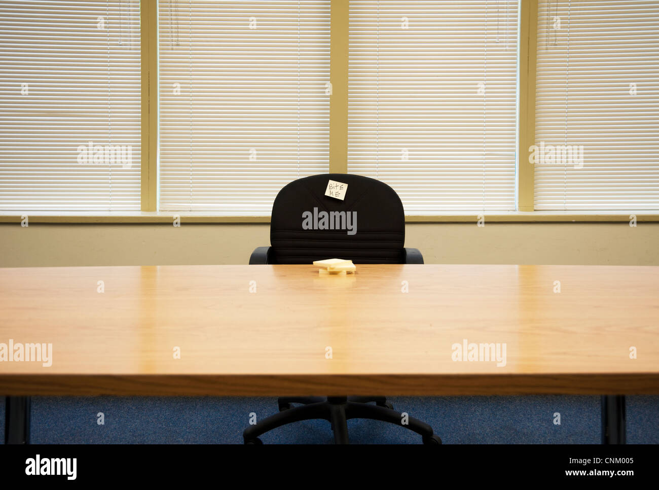 Empty chair at boardroom table with sticky note that says 'bite me' - Stock Image