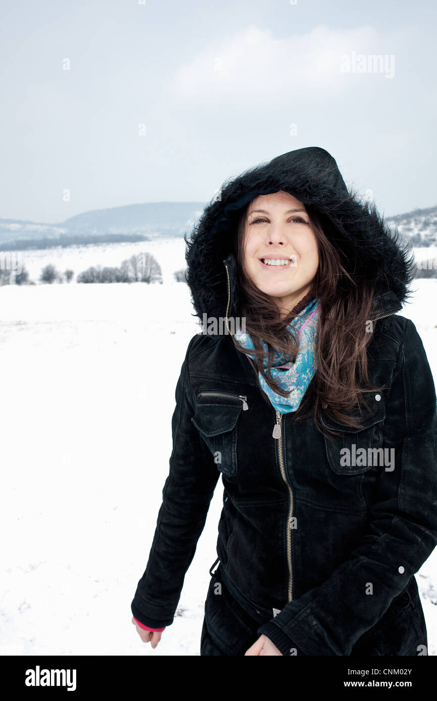 Woman in parka walking in snow - Stock Image