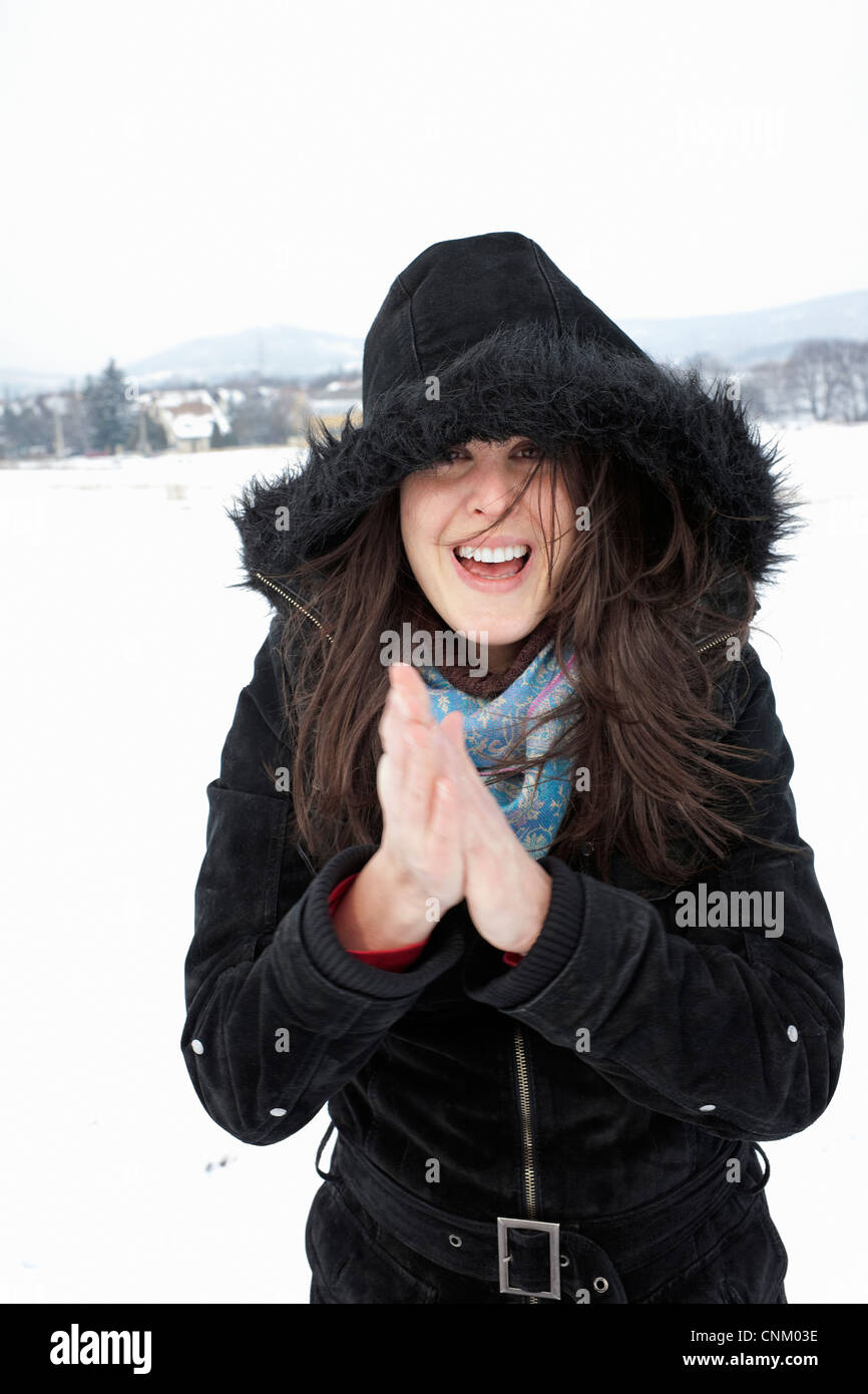 Woman wearing parka in snow - Stock Image
