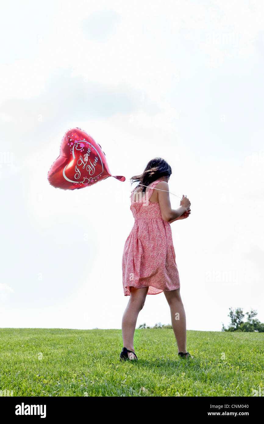 Teenager carrying heart-shaped balloon - Stock Image