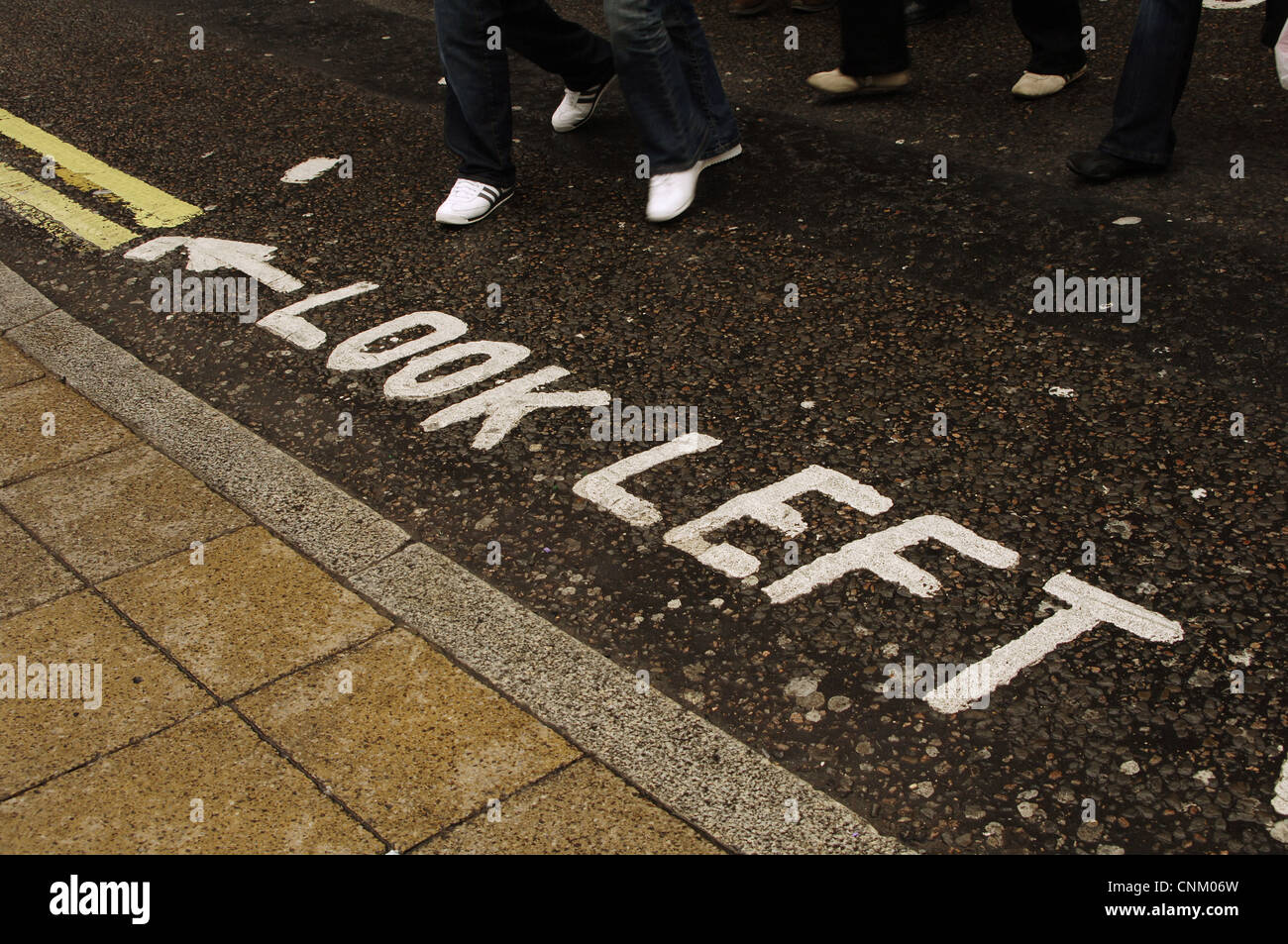 United Kingdom. London. Warning on the road of the obligation to look left before crossing the street. West End. - Stock Image
