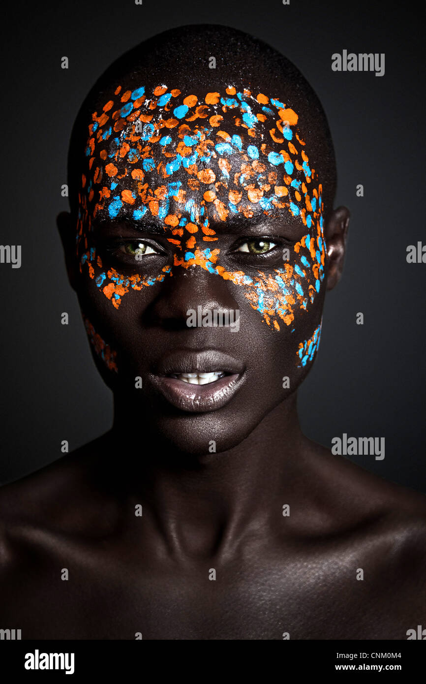 African Black Young Male Model Wearing Creative Orange And Blue Tribal Paint On Face Photographed In A Studio Environment