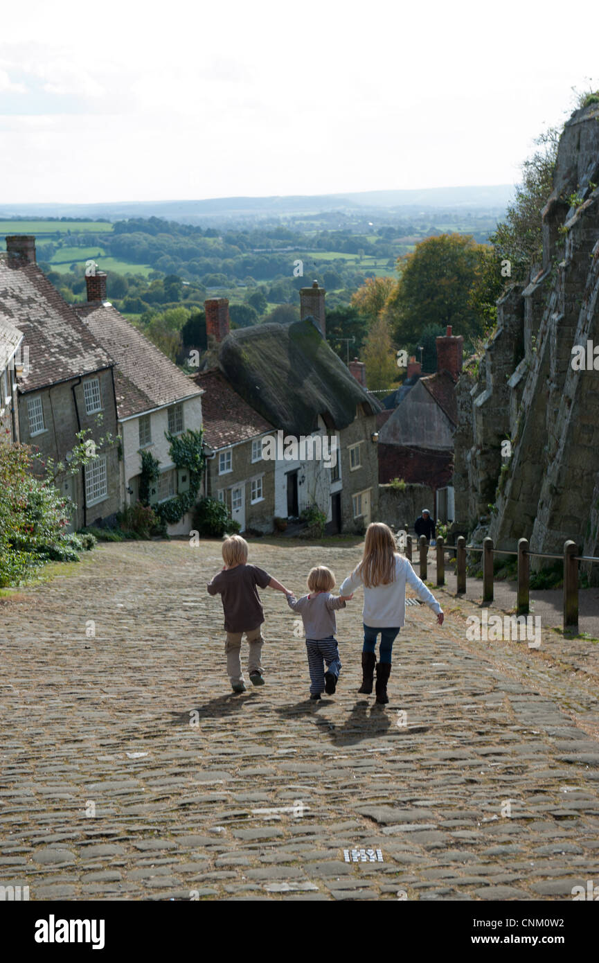 Children walking up Gold Hill in Shaftesbury, made famous by the Hovis advert directed by Ridley Scott - Stock Image