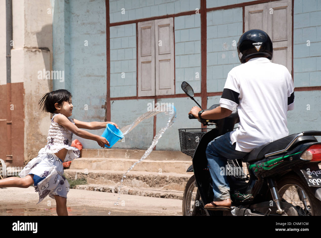 Burmese girl enjoying the water festival by throwing a bucket of water at a passing motorcyclist. Kalaw, Burma. - Stock Image