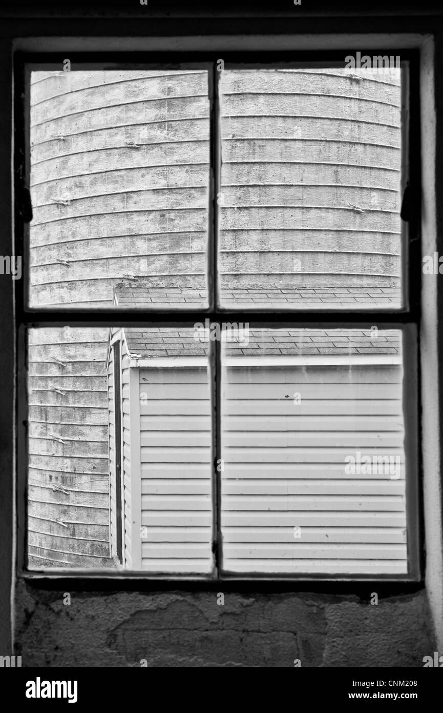Side of a silo through a window pane of a dairy - Stock Image