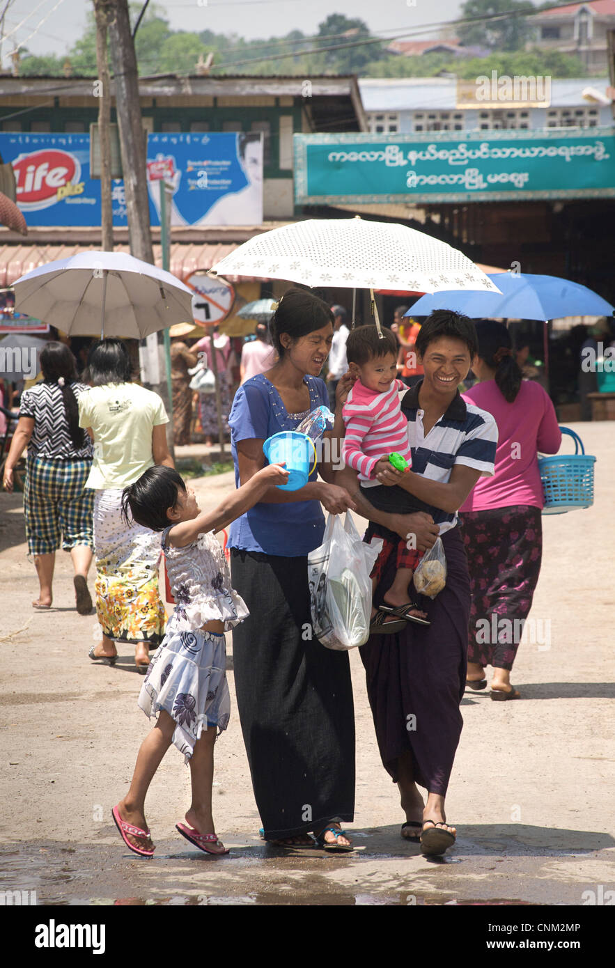 Burmese girl enjoying the water festival by throwing a bucket of water at a passing couple with child. Kalaw, Burma. - Stock Image
