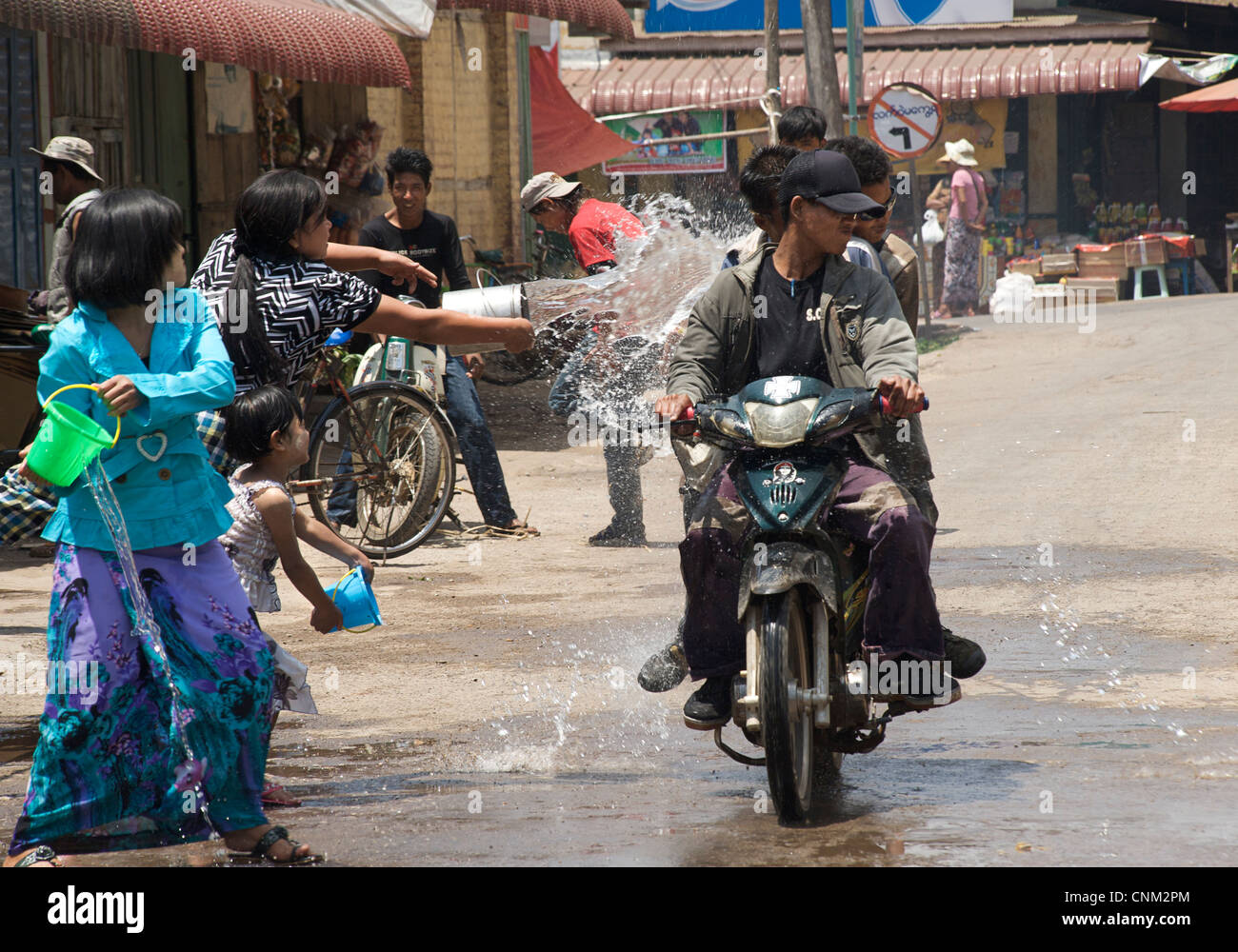 Burmese girls enjoying the water festival by throwing a bucket of water at a passing motorcyclist. Kalaw, Burma. - Stock Image