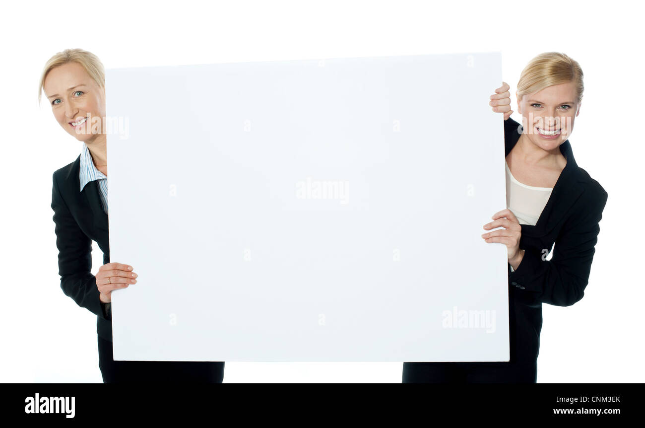 Female business representatives presenting a clipboard isolated over white background - Stock Image