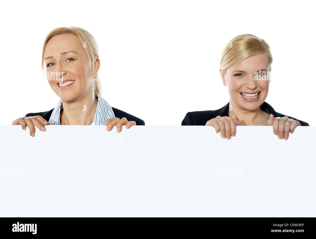 Smiling corporate women showing blank banner ad to camera - Stock Image