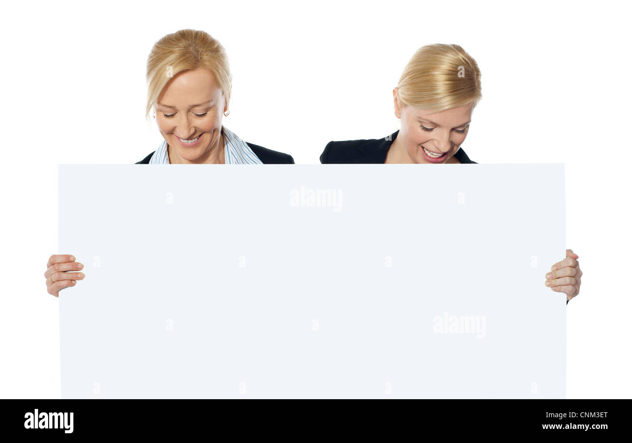 Female business executives looking down at blank banner ad - Stock Image