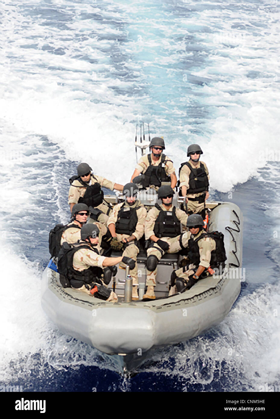 US Navy sailors assigned to the Visit, Board, Search and Seizure team operate in a rigid hull inflatable boat April - Stock Image