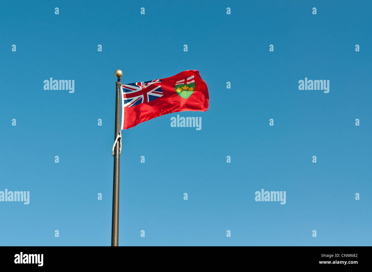 The provincial flag of Ontario flies on a flagpole with a deep blue sky in the background. - Stock Image