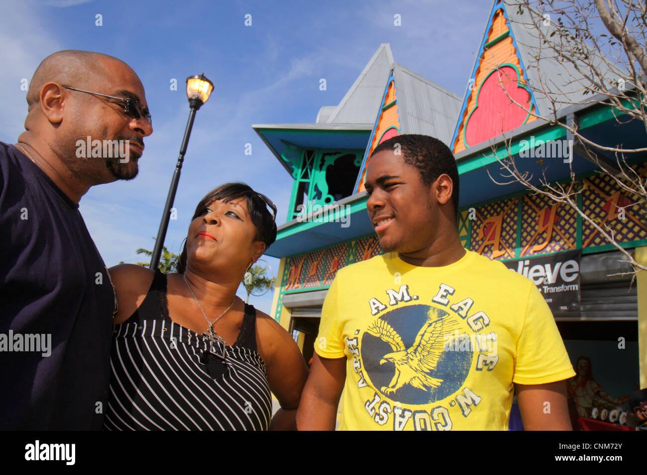Miami Florida Little Haiti Caribbean Market Place Carnival marketplace community event Black man woman son family - Stock Image