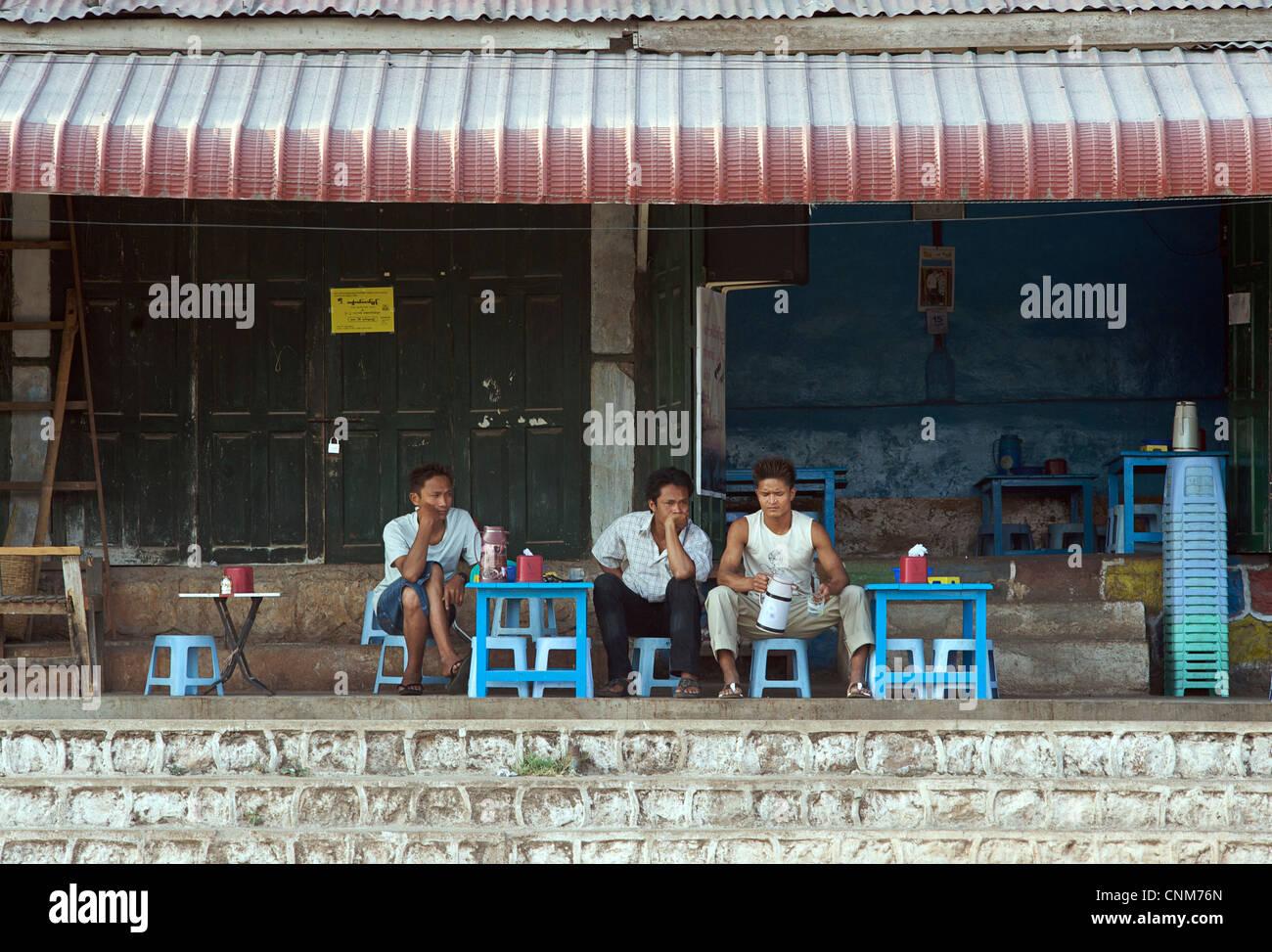 Burmese men siting at a table outside a roadside tea shop. Kalaw, Burma - Stock Image