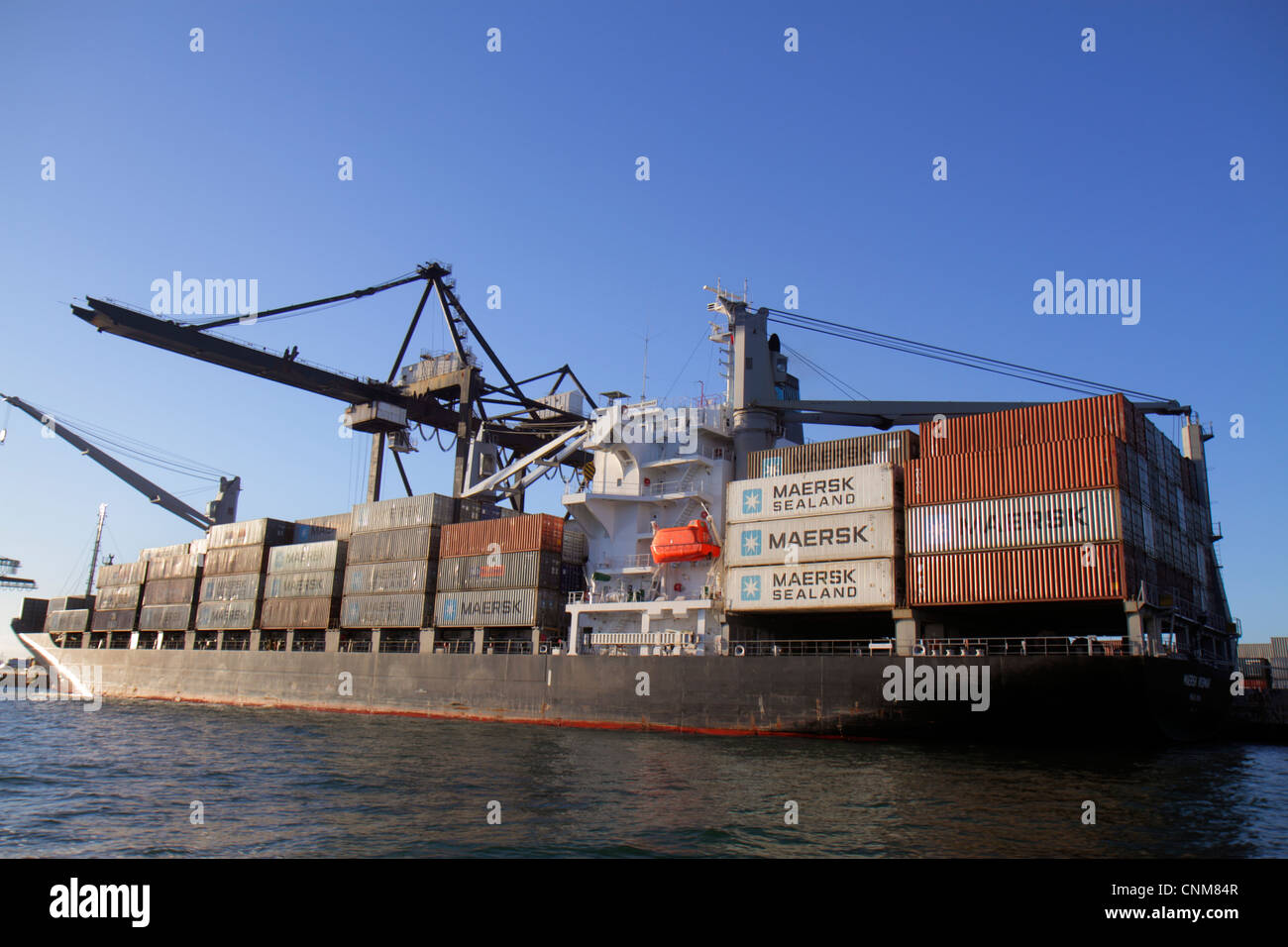 Miami Florida Biscayne Bay Dodge Island Port of Miami cargo container lift cranes ship Maersk Sealand - Stock Image