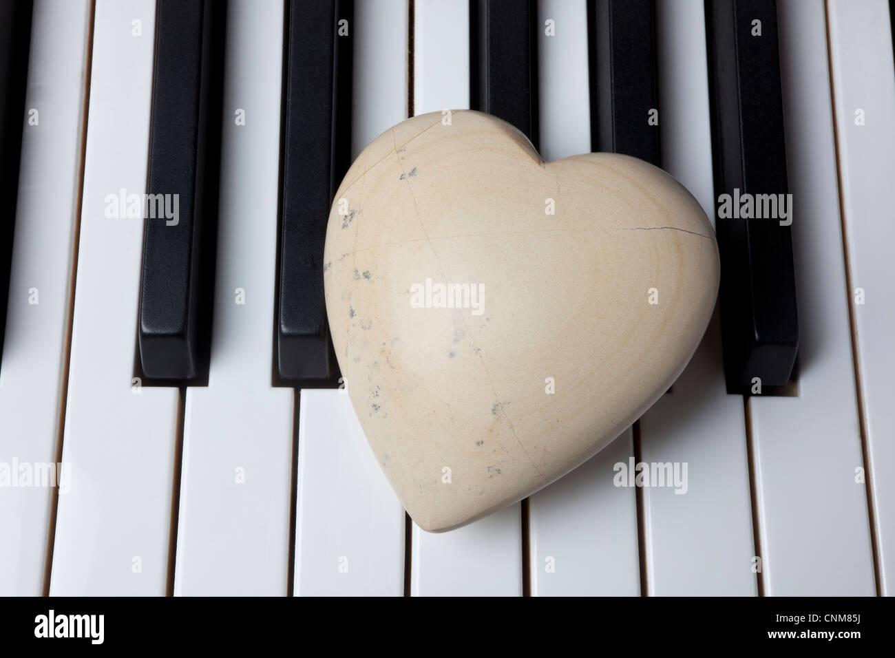 White stone heart on piano keys - Stock Image