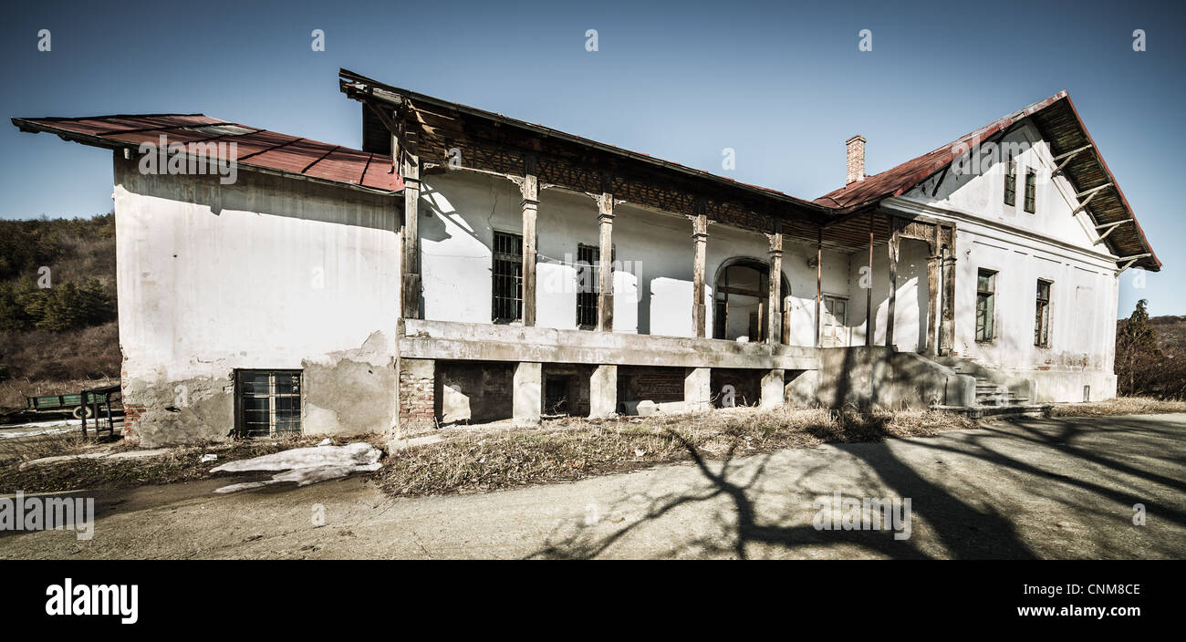 Moody split toned landscape with a decrepit house - Stock Image