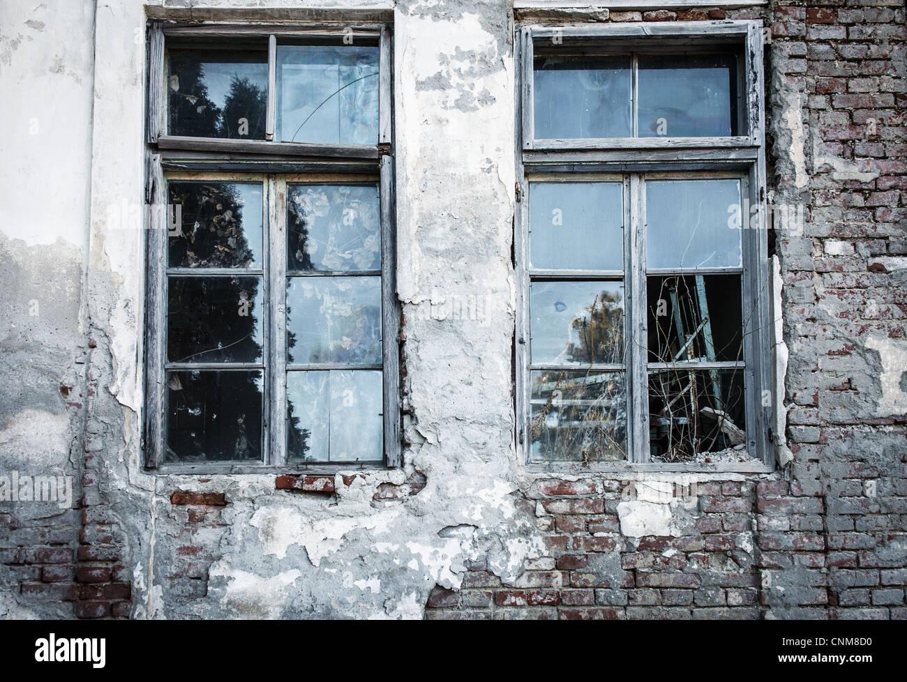 Broken window on an old decrepit building Stock Photo