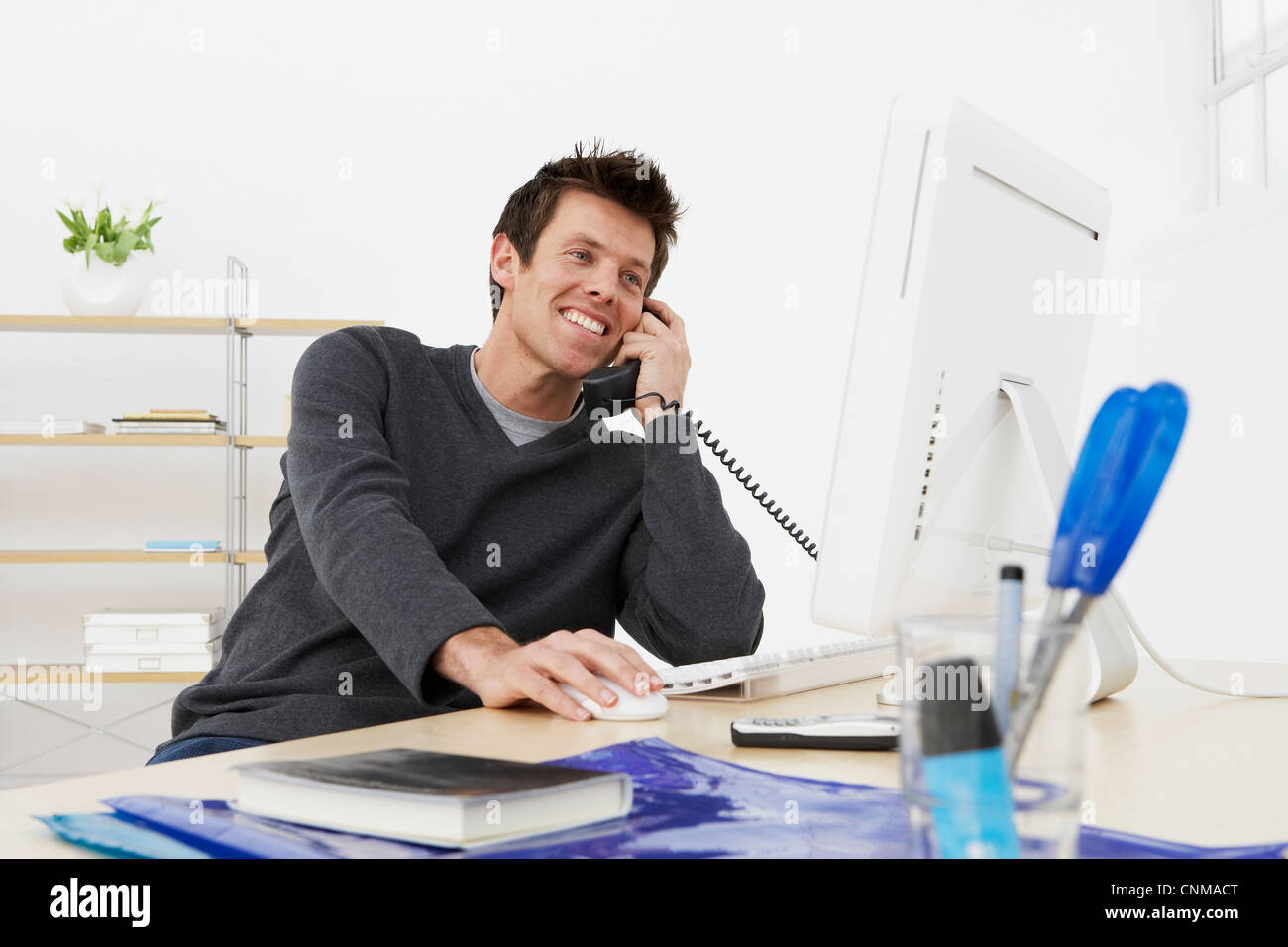 Businessman talking on phone at work - Stock Image