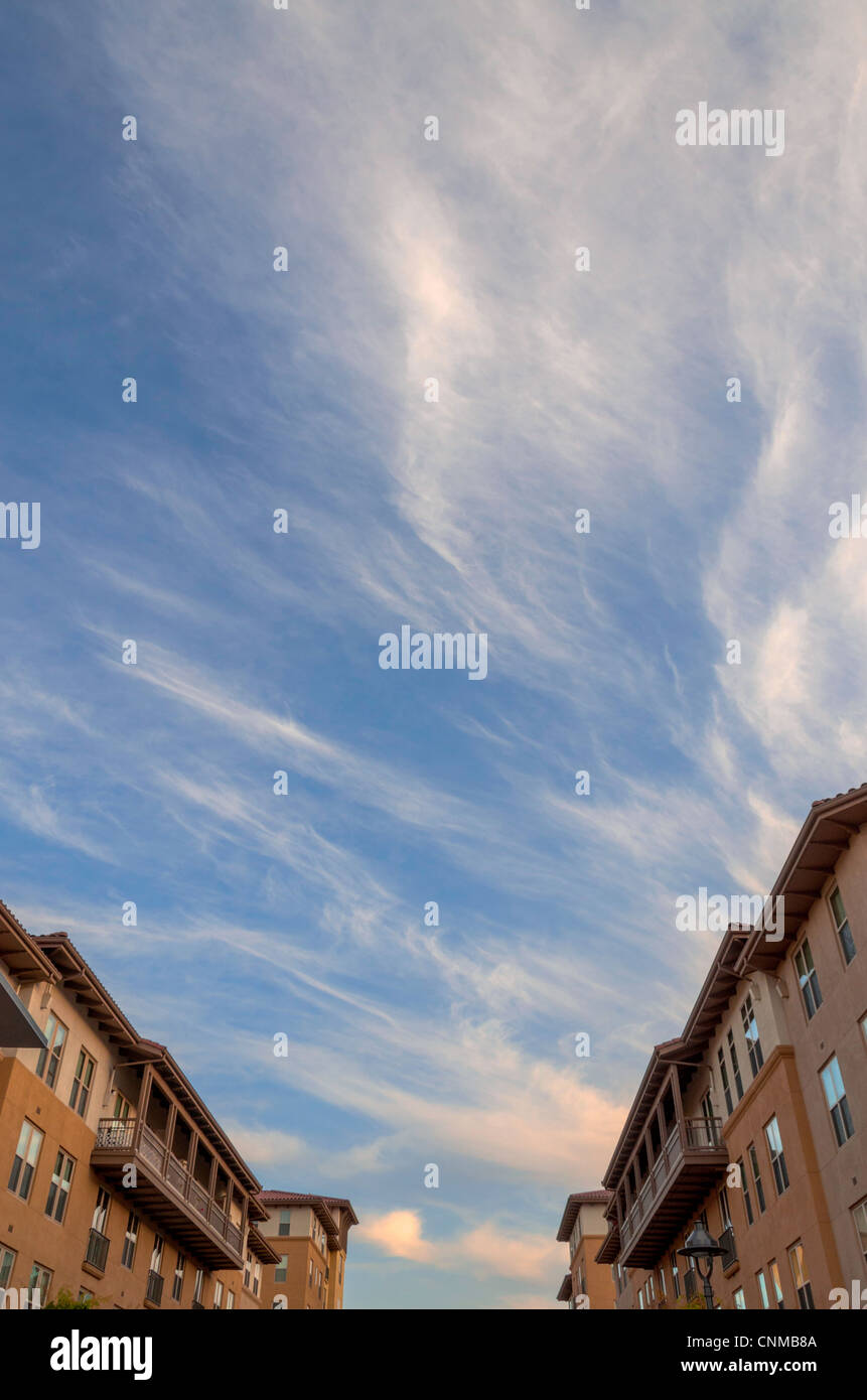 Partly cloudy sky between two buildings. - Stock Image
