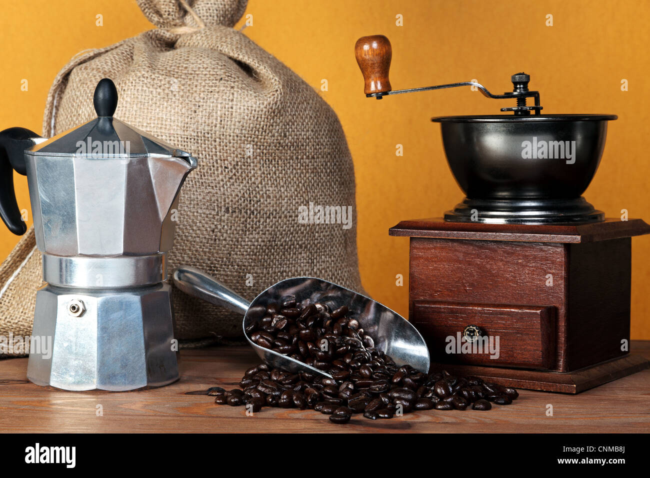Still life photo of a caffettiera or moka pot with traditional coffee grinder hessian sack and arabica beans in - Stock Image