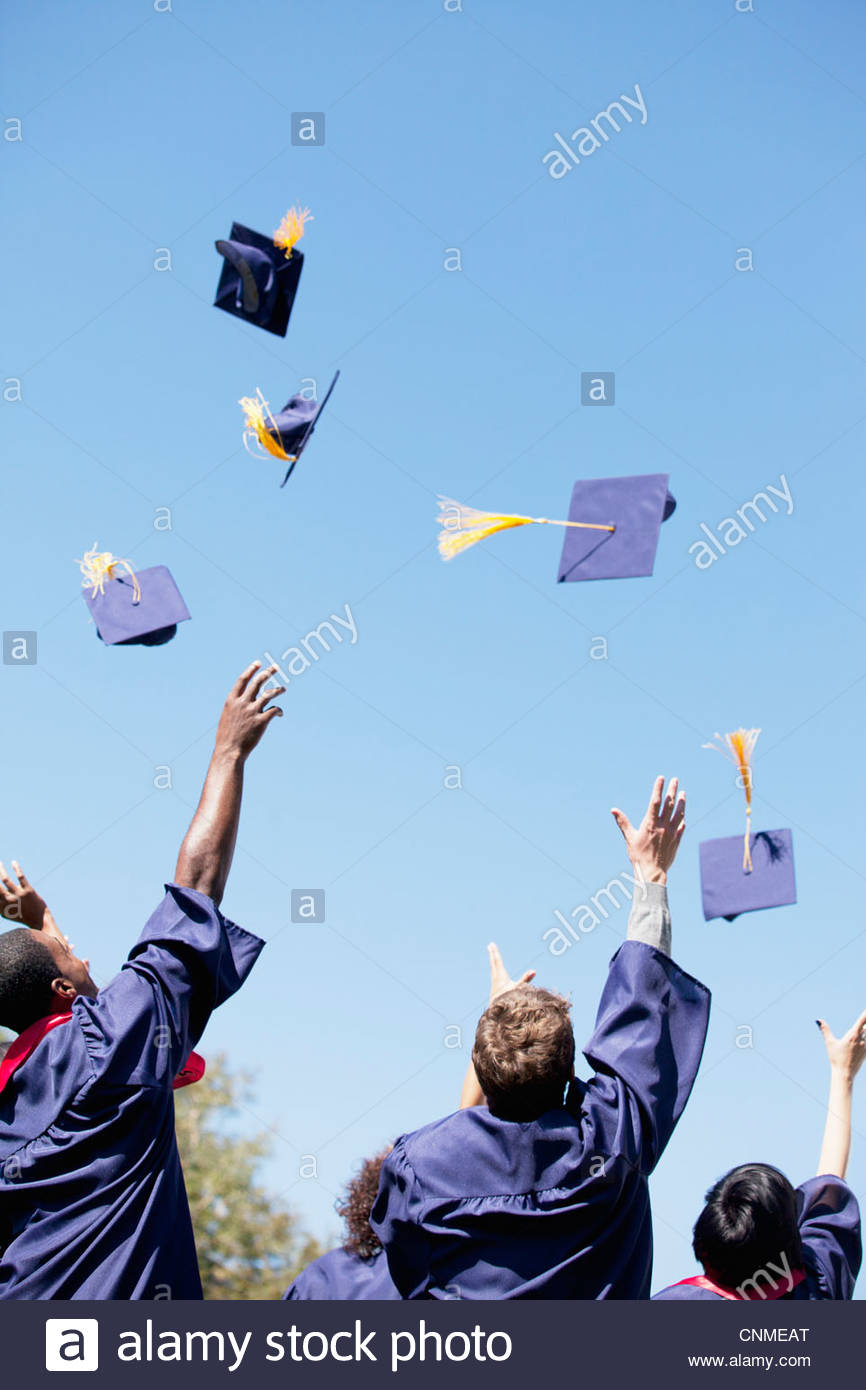 Graduates throwing caps in air outdoors - Stock Image