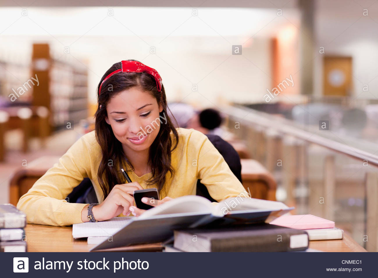 Student using cell phone and studying in library - Stock Image