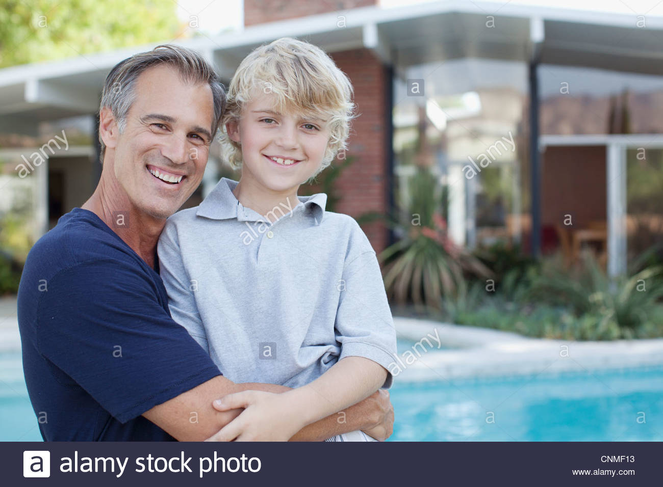 Father and son hugging by pool - Stock Image