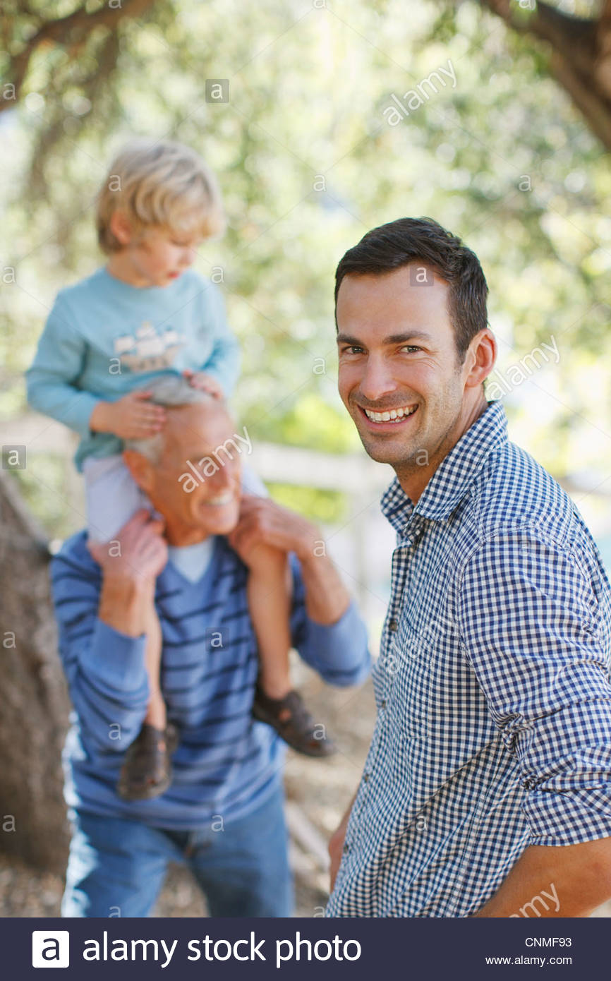 Three generations of men relaxing outdoors - Stock Image