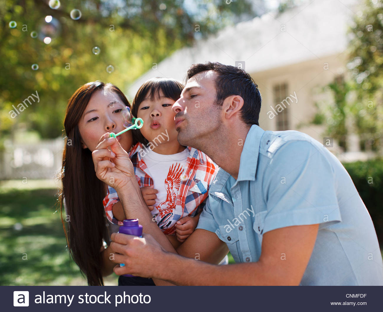 Family blowing bubbles together outdoors Stock Photo
