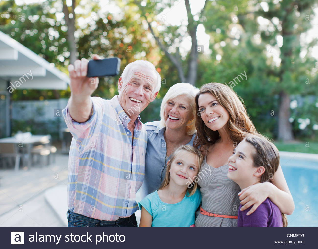 Family taking picture of themselves outdoors - Stock Image