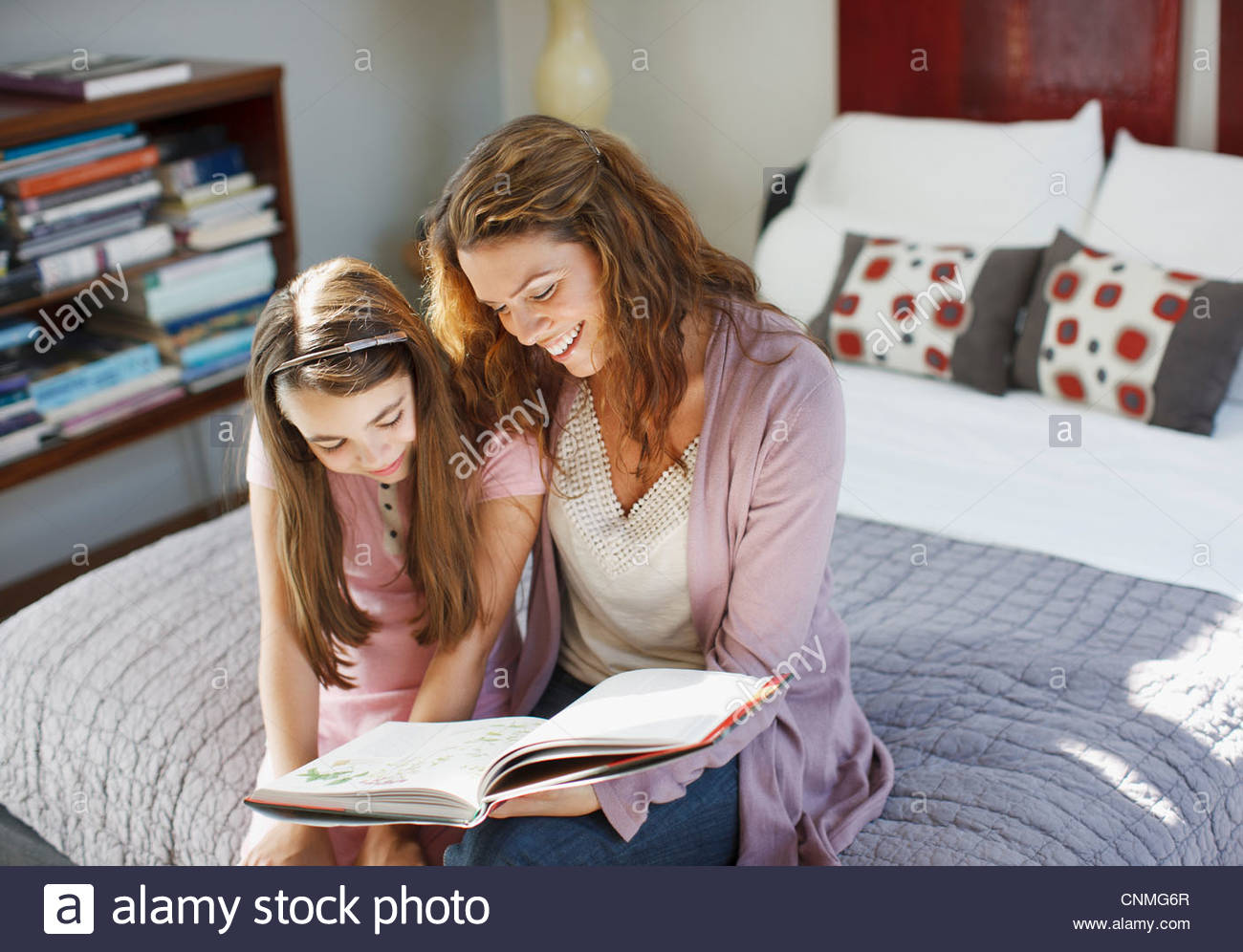 Mother and daughter reading on bed - Stock Image