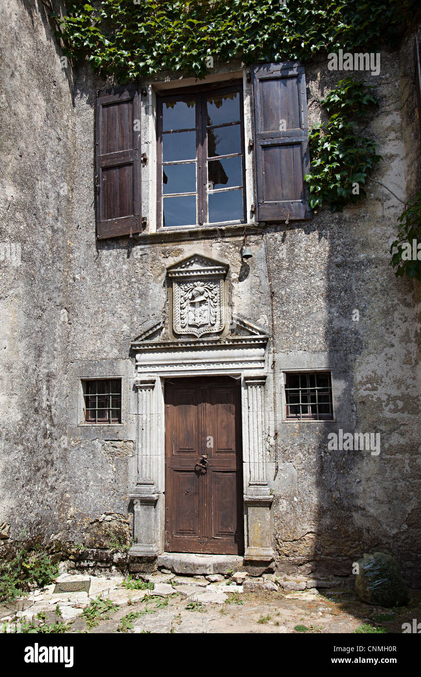 Old door with family crest containing helmet, Cite de la Couvertoirade, Aveyron, France - Stock Image