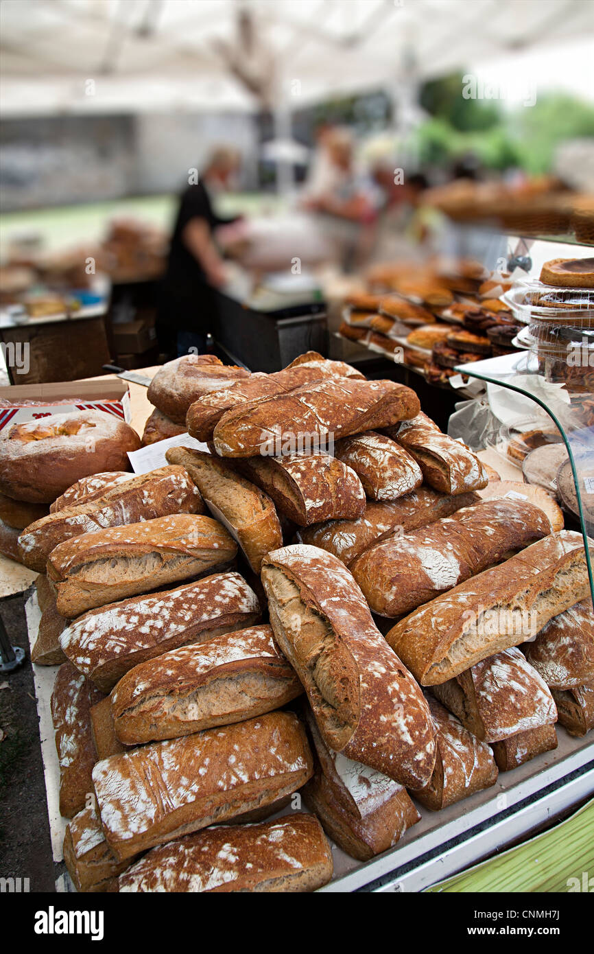 Artisan bread on sale at market stall with people in background, France - Stock Image