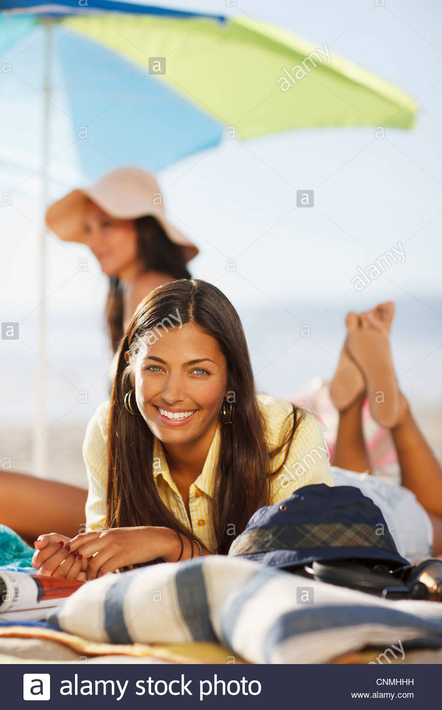 Smiling woman sunbathing on beach - Stock Image