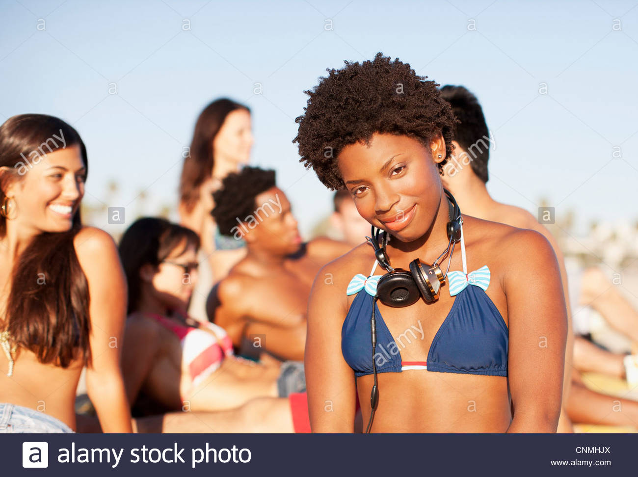 Woman wearing headphones on beach - Stock Image