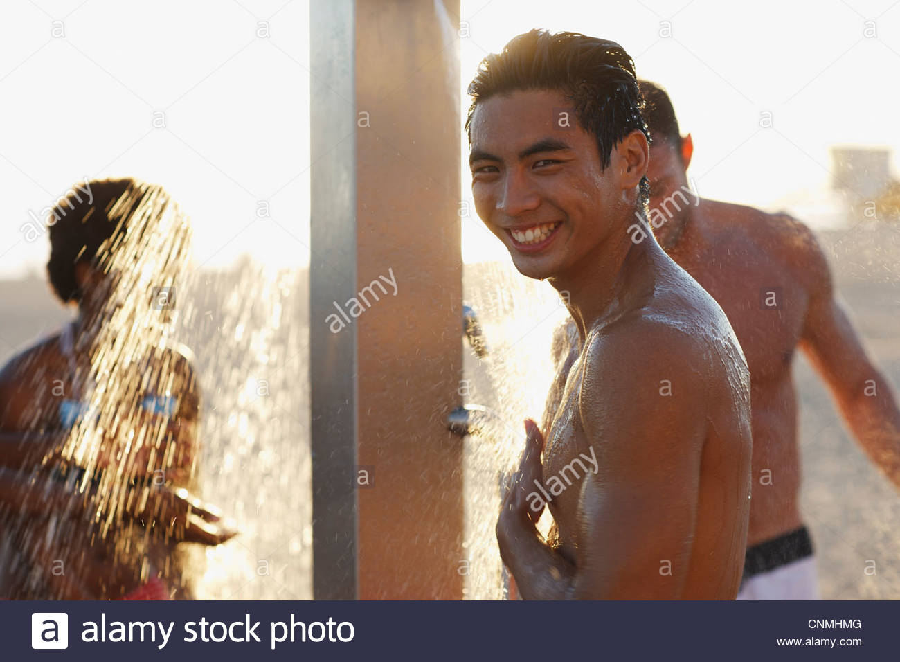 Men in swimsuits showering on beach - Stock Image