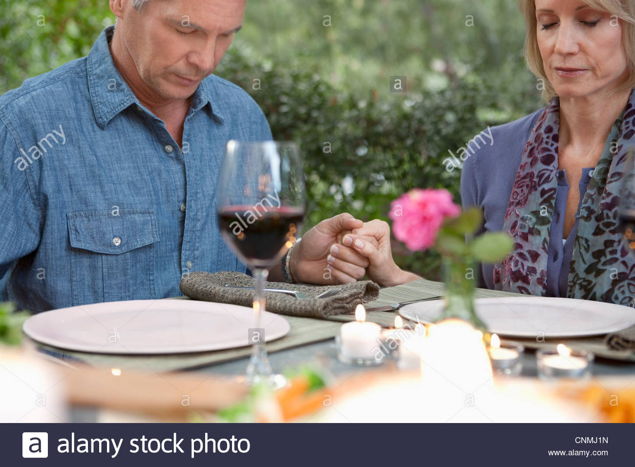 Older couple praying at dinner table - Stock Image