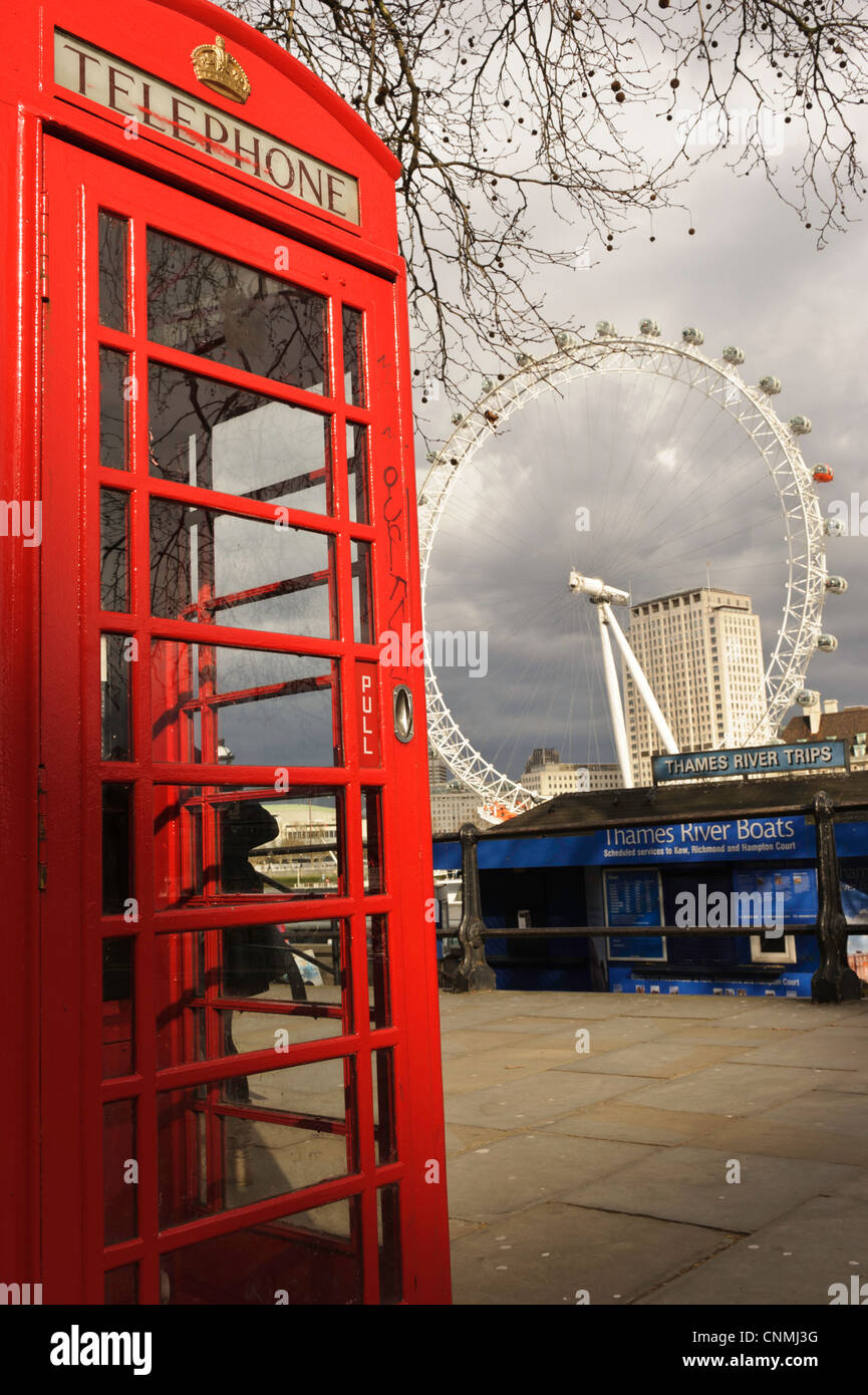 A red British telephone box with the London Eye in the background on the other side of the Thames - Stock Image