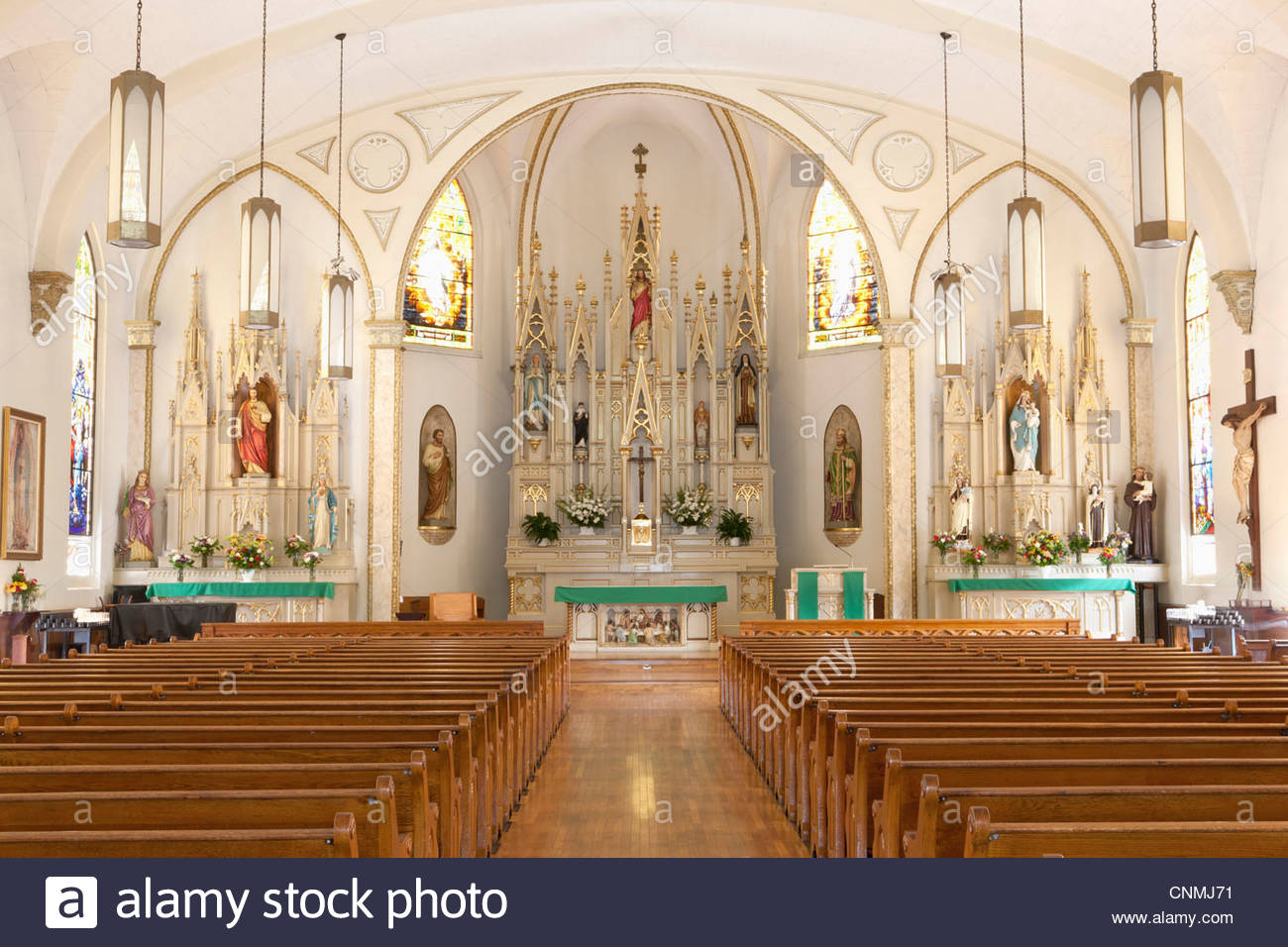 Pews and altar in empty ornate church - Stock Image