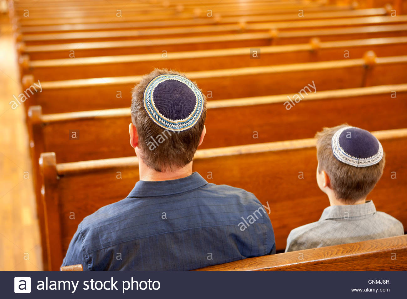 Father and son in yarmulkes sitting in synagogue - Stock Image