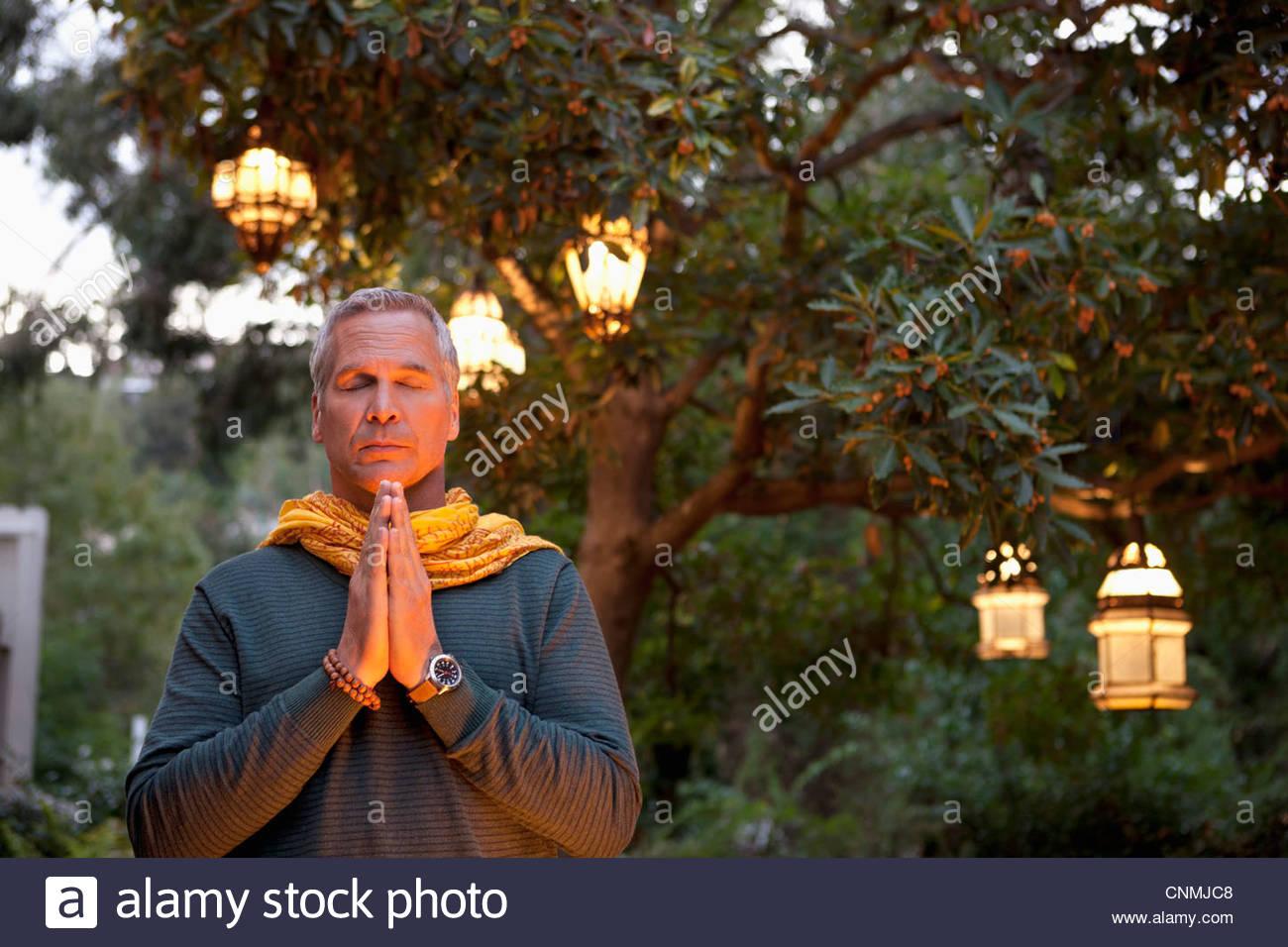 Older man praying in backyard - Stock Image