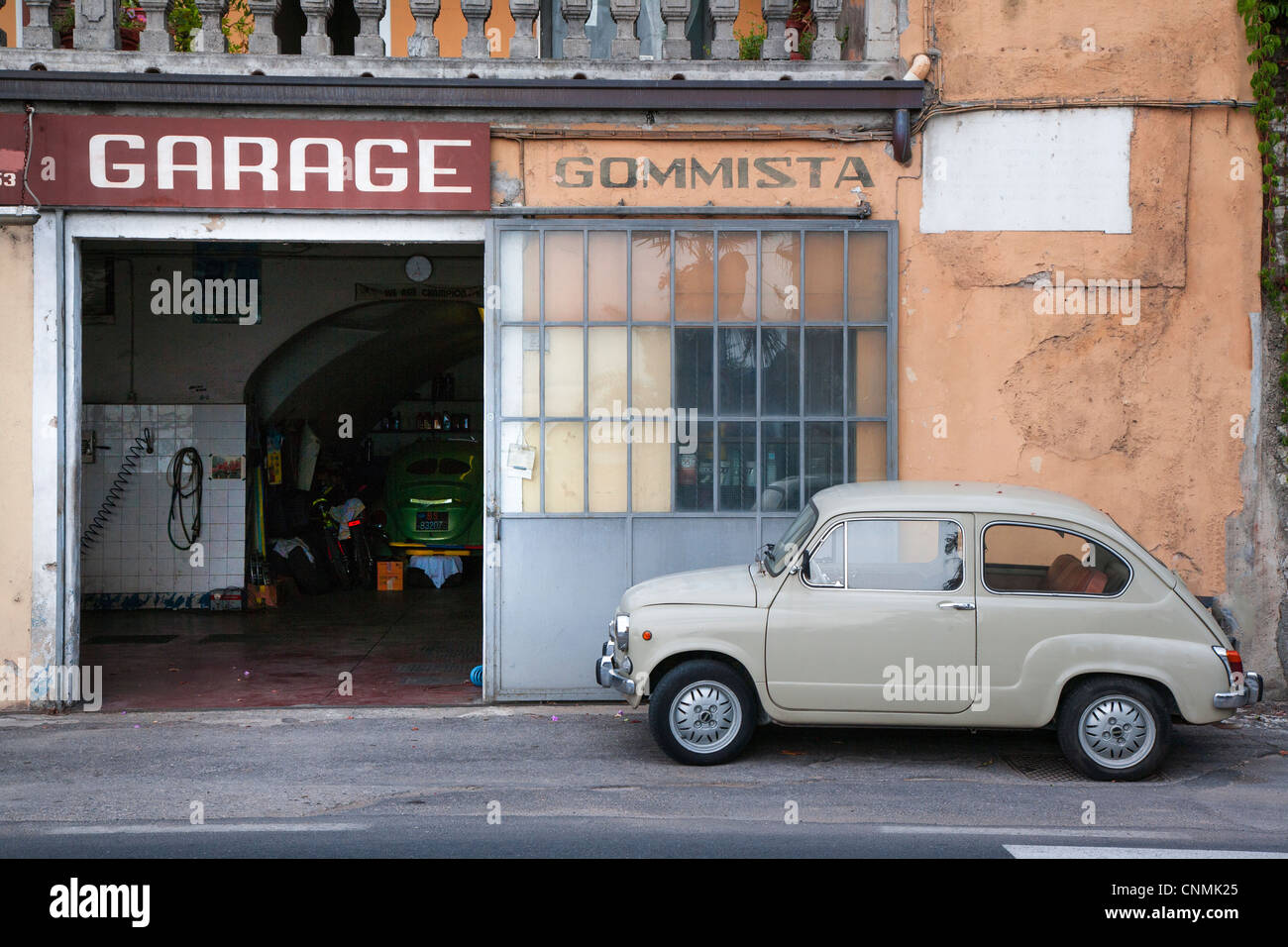 Old Italian Fiat parked outside a garage in Italy - Stock Image