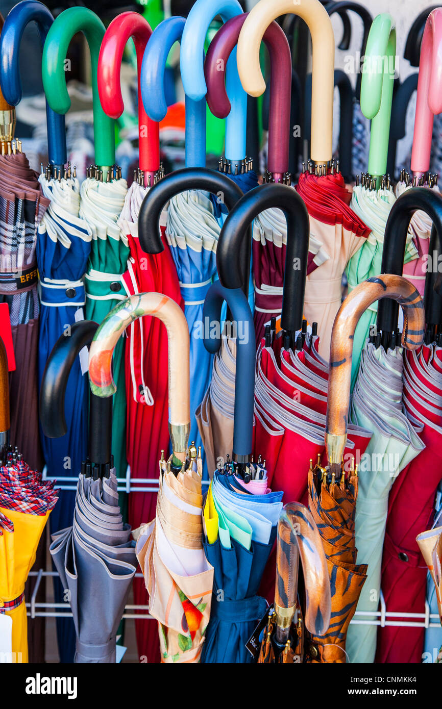 Umbrellas lined up for sale on a stand in Italy - Stock Image