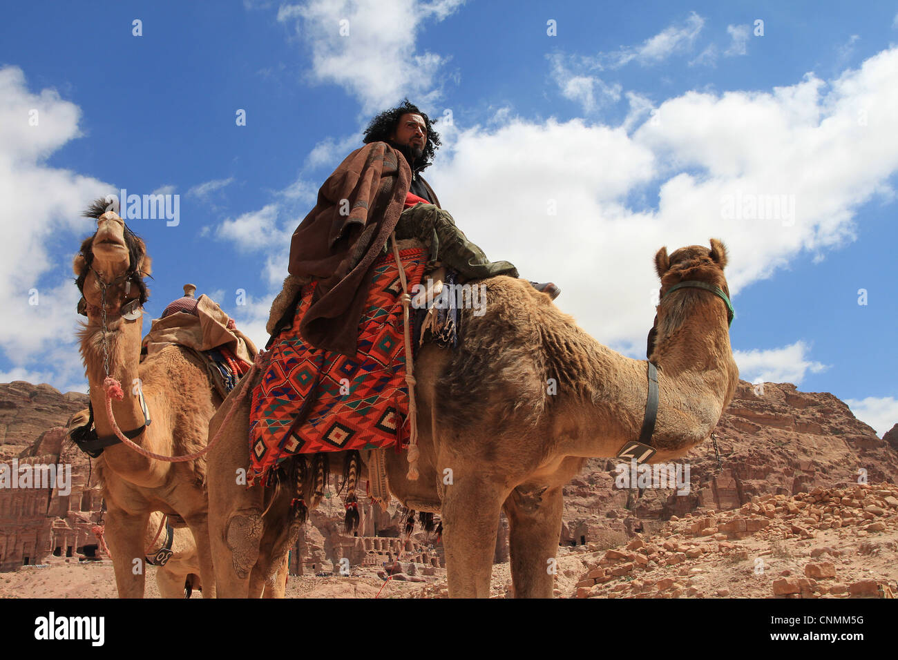 A Bedouin in front of the Royal tombs in Petra trying to hire tourists for a ride with his camels, Jordan. Stock Photo
