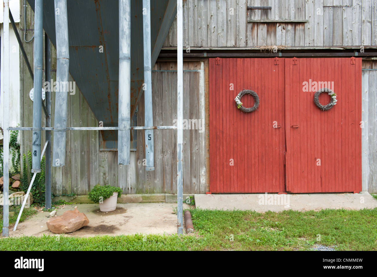 Red barn doors with wreaths hanging on them on a barn next to an old grain bin - Stock Image