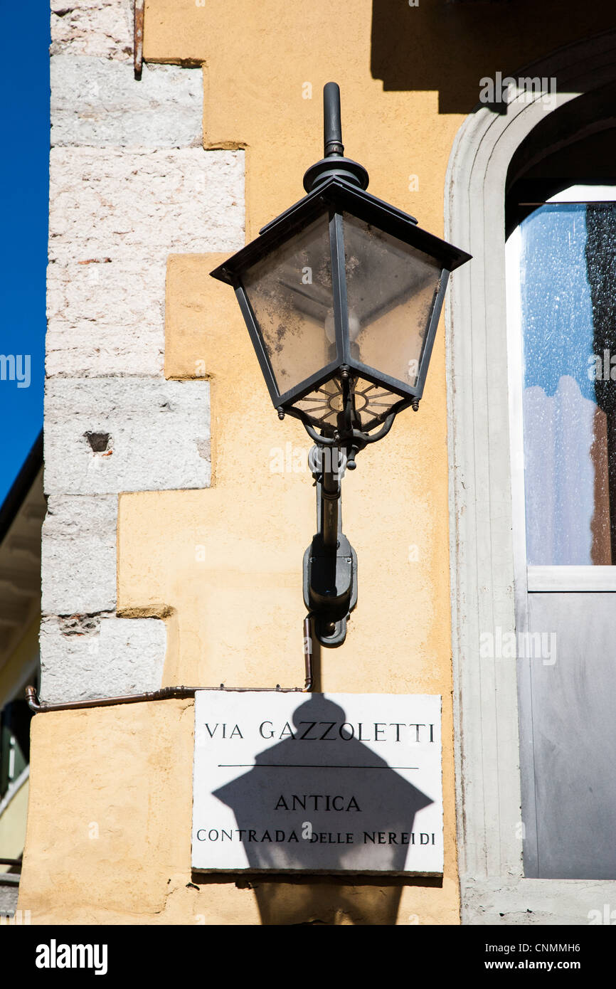 Wrought iron lamp and street sign in Italy - Stock Image