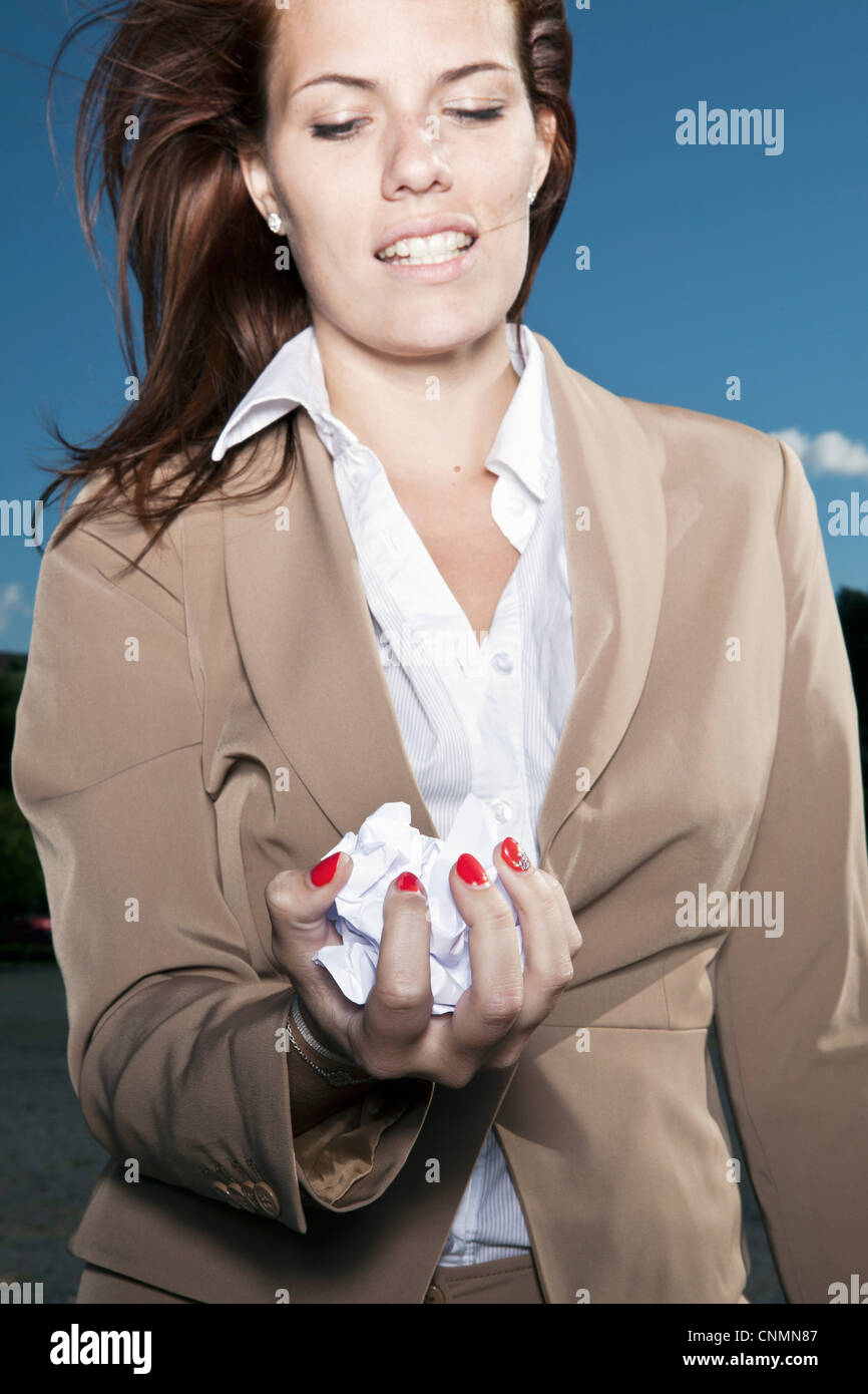 Businesswoman holding crumpled paper - Stock Image
