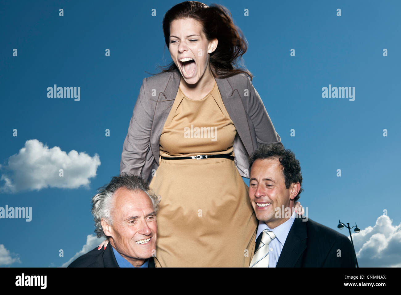 Businesswoman climbing on colleagues - Stock Image