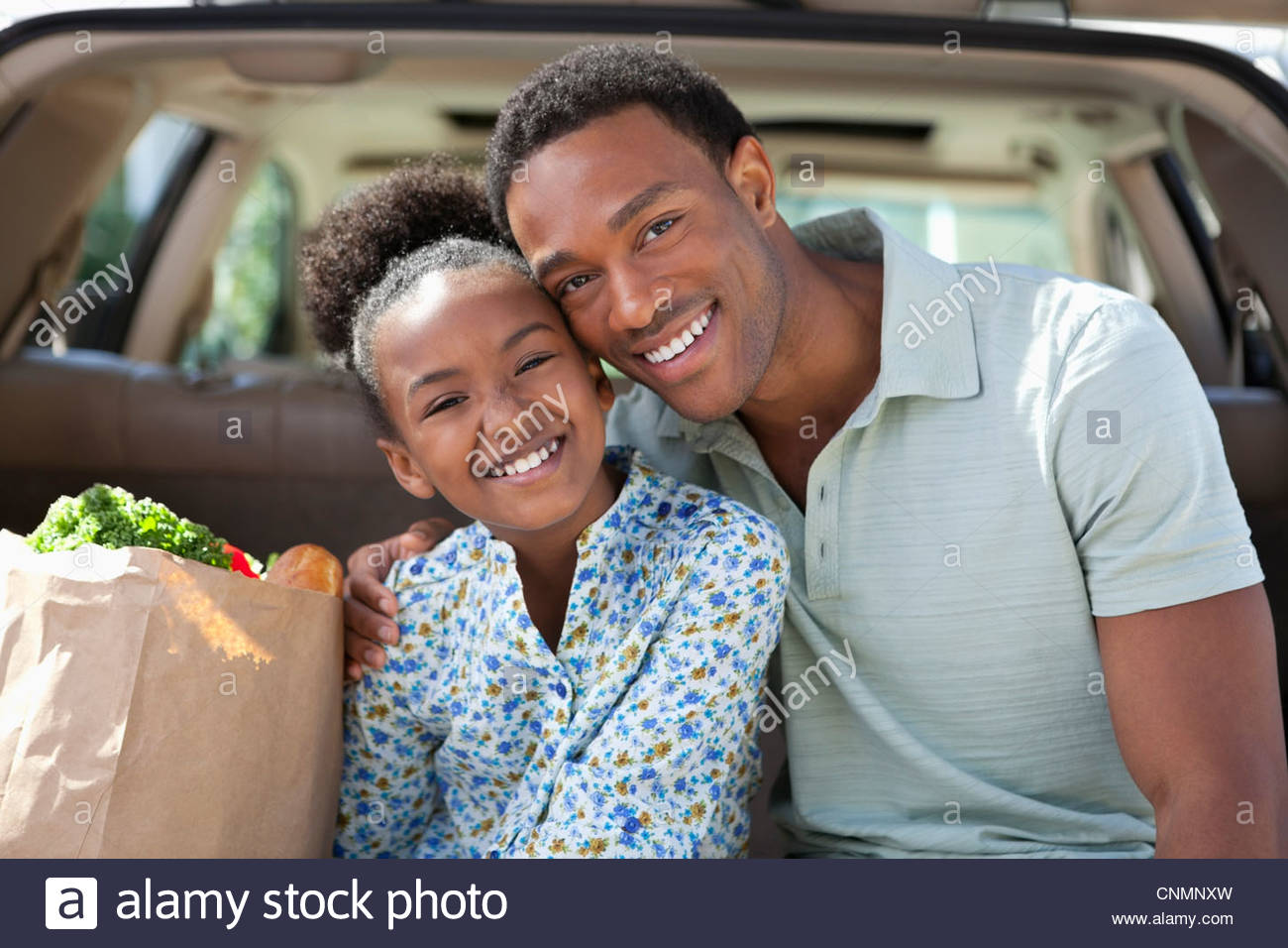 Father and daughter unloading groceries from car - Stock Image